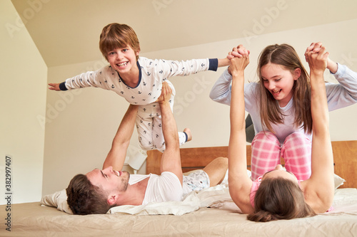 Obraz na plátně Parents play with their children in bed in the morning