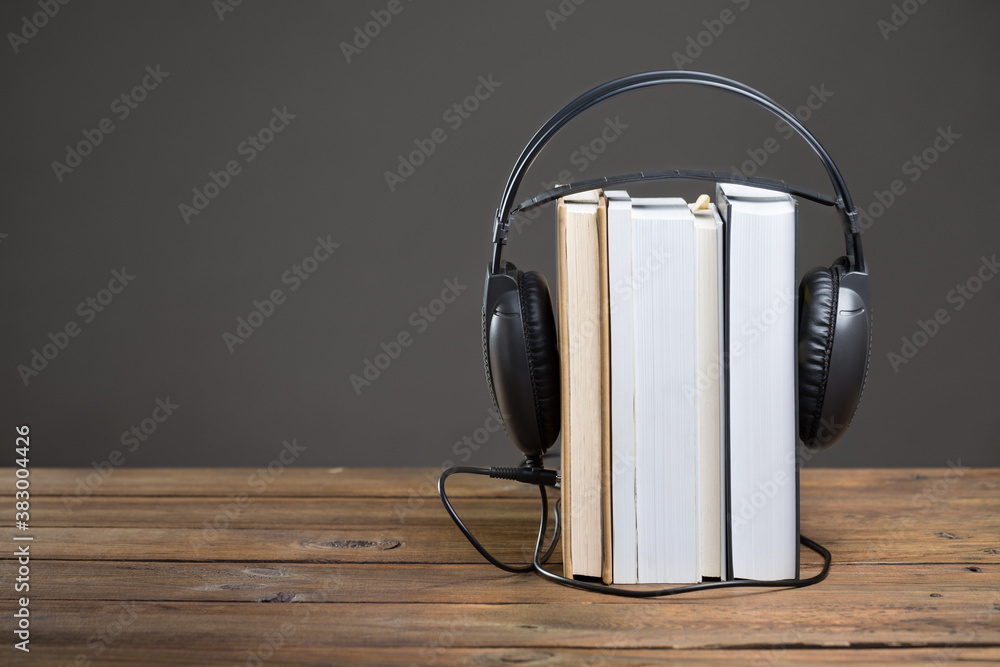 Fototapeta Books and headphones on wooden table in audiobook concept