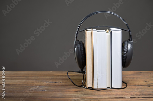 Fotografie, Obraz Books and headphones on wooden table in audiobook concept