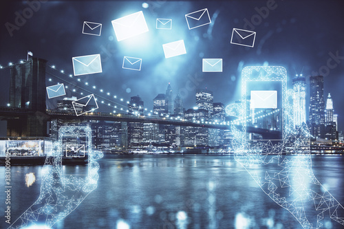 Double exposure of envelop hologram flying from gadget and city view background. Concept e-mail.