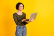 Leinwandbild Motiv Photo of positive lady chatting on laptop wear green sweater isolated over bright yellow color background