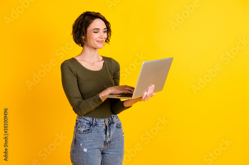 Photo of positive lady chatting on laptop wear green sweater isolated over bright yellow color background