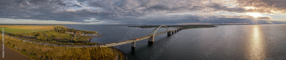 Fototapeta Panorama aerial view of  Fehmarn Sound Bridge in sunset (Fehmarnsundbrücke), suspension bridge with steel arches connecting the German mainland with the island in the Baltic Sea.