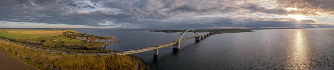 Panorama aerial view of Fehmarn Sound Bridge in sunset (Fehmarnsundbrücke), suspension bridge with steel arches connecting the German mainland with the island in the Baltic Sea.