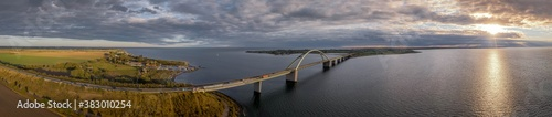 Fotografía Panorama aerial view of  Fehmarn Sound Bridge in sunset (Fehmarnsundbrücke), suspension bridge with steel arches connecting the German mainland with the island in the Baltic Sea