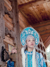 A Girl In A Snow Maiden Costume Stands Against The Background Of A Winter Forest And A Wooden House. Winter, December. Russian Christmas Character Snegurochka. New Year.