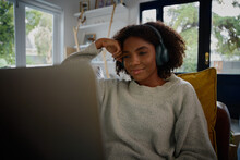 Smiling Young African Woman Watching Webinar On Laptop With Headphones At Home
