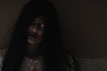 Female Zombie In Blood. Closeup Face And Eyes Of Asian Woman Ghost With Blood. Horror Creepy Scary Fear In A Dark House. Hair Covering The Face, Halloween Festival Concept
