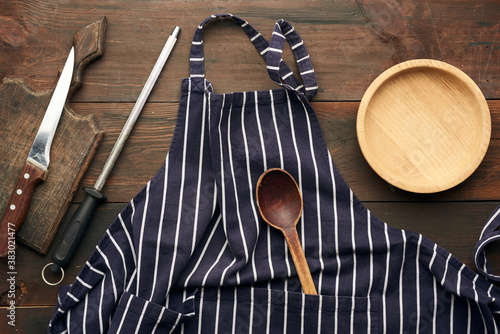 Obraz na plátně blue textile kitchen apron with white stripes and kitchen utensils, top view