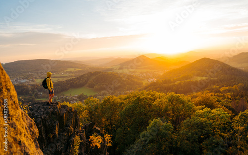A hiker walking on a mountain meadow in spring or autumn. Hiking in the Lusatian mountains. Hiker, Backpacking on top of a mountain cliff landscape and trekking in it. Concept: Adventure, Art, Travel