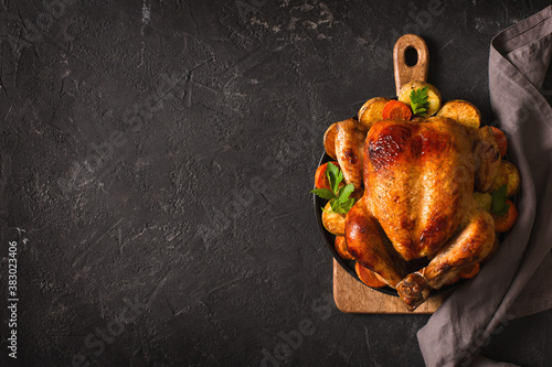 Fototapeta Fall thanksgiving table with roasting chicken or turkey food on black background