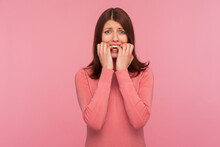 Nervous Confused Brunette Woman In Pink Sweater Biting Nails On Her Fingers In Panic, Depression, Sadness. Indoor Studio Shot Isolated On Pink Background