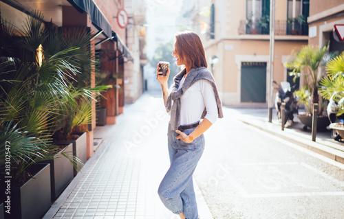 Fototapeta Smiling caucasian woman in trendy wear spending time on urban setting drinking c