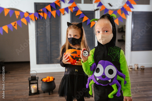 Obraz na plátně Children in Halloween costumes and with masks on their faces play