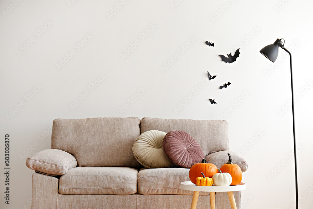Bunch of classic orange, hooligan and baby boo pumpkins on coffee table, bat shaped decorations on the wall as symbol of autumnal holidays season. Living room interior background, Close up, copy space