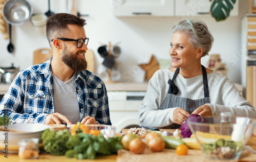 Photo Happy mature woman with adult son cooking together at home.