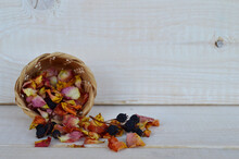 Wicker Basket With Dried Rose Petals And Dark Blue Berries On A White Wood Background
