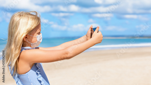 Fototapeta Funny girl taking selfie photo by smartphone on tropical sea beach