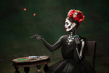 Gambling. Young Girl Like Santa Muerte Saint Death Or Sugar Skull With Bright Make-up. Portrait Isolated On Dark Green Studio Background With Copyspace. Celebrating Halloween Or Day Of The Dead.