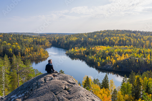 Obraz na plátně The man on top of a rock in the autumn forest on a background of a beautiful lake