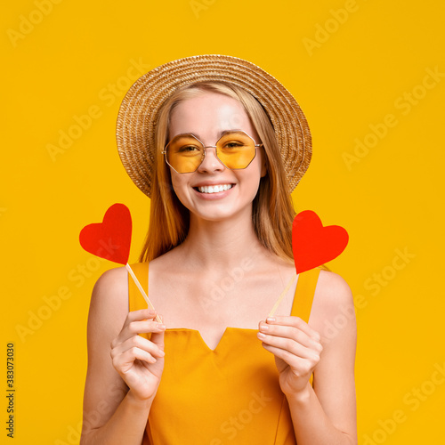 Lovely teen girl in hat and sunglasses holding two red hearts Canvas Print