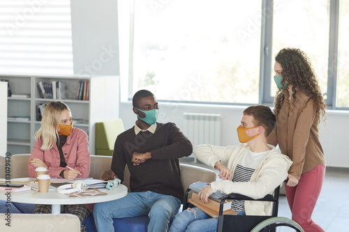 Foto Side view at multi-ethnic group of students wearing masks while studying in coll