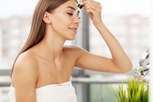 Attractive Young Woman Applying Serum On Face With Pipette