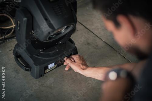 Papel de parede Theater lighting technician electric engineer adjusting focus of lighting elements backstage