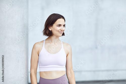 Fotomural glückliches Portrait eines Mädchen/Frau in Sportkleidung vor moderner Architektu