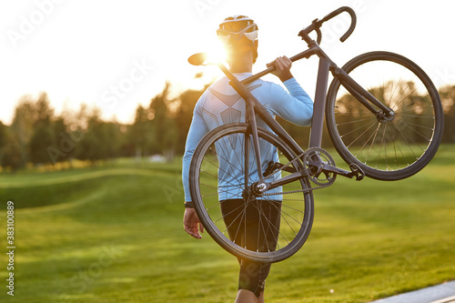 Foto Strong athletic man in sportswear carrying his bicycle and watching amazing suns