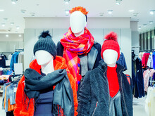 Three White Mannequins Without A Face In Winter Clothes Stand In A Store