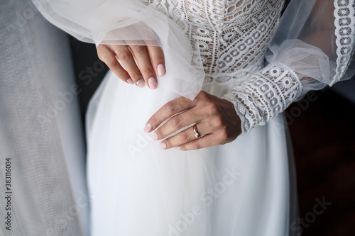 Gentle female hands of the bride with a gold wedding ring on the ring finger