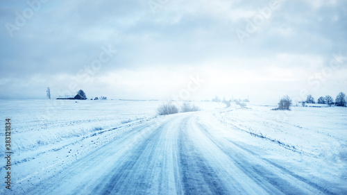 Fototapeta Snow-covered S shape country road through the fields after a blizzard at sunset. Old rustic house in the background. Winter rural scene. Dramatic sky, colorful cloudscape. Ice desert. Lapland, Finland obraz
