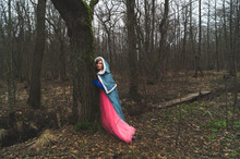 Woman With Mantle Leaned Against A Tree. Adult Woman In Fantasy Costume With Cape