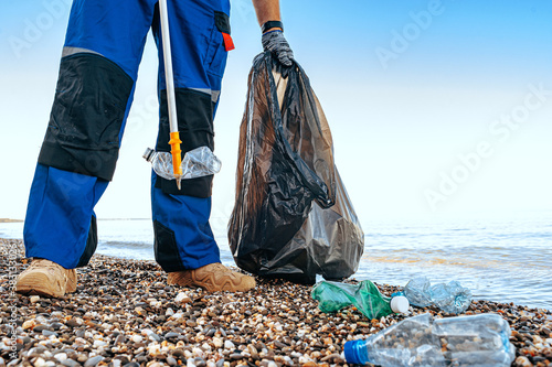 Close up photo of a man collecting garbage with a grabbing tool on the beach Wallpaper Mural
