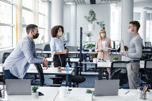 Modern team meeting, group work and social distancing. Manager with tablet speaks with workers in protective masks in interior of modern office with gadgets