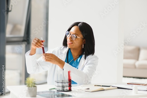 Obraz na plátně Young beautiful African American girl doctor in a white coat with a stethoscope