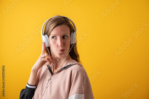 Obraz na plátně Young woman wearing white headphones making a goofy face