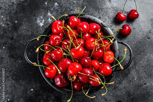 Fotografia Red ripe cherries in a colander. Black background. Top view.
