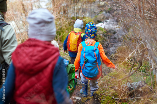 group of children with backpacks walking along mountain path