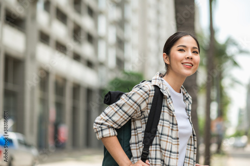 Smiling young asian beautiful woman backpacker traveling take time in holiday in urban city avenue Canvas Print
