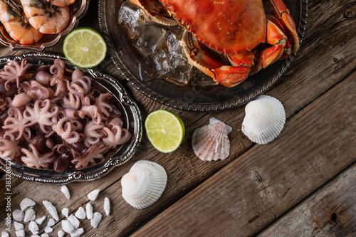 Fototapeta Top view of plates with cooked crab, octopuses and large shrimps served with lime, seashells and sea salts on wooden rustic background. Seafood concept. Organic food. Italian cuisine. obraz