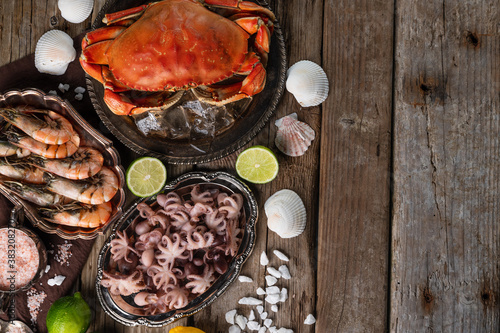 Fototapeta Top view of plates with cooked crab, octopuses and large shrimps served with lime, seashells and sea salts on wooden rustic background. Seafood concept. Organic food. Traditional Italian meal. obraz