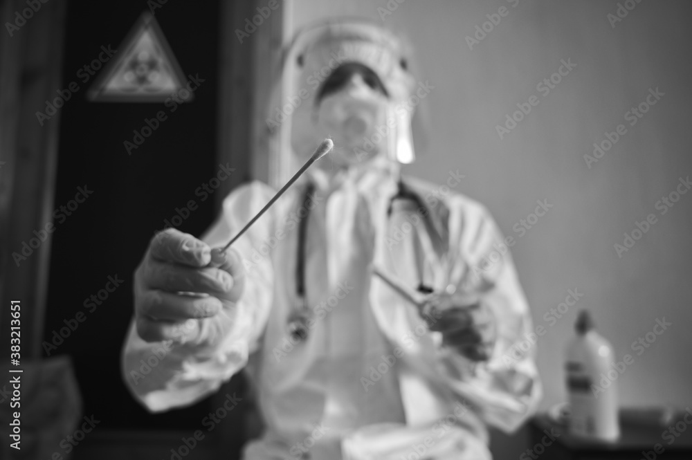 Fototapeta Medical worker holding COVID-19 swab collection kit, wearing white PPE protective suit, face mask, gloves, test tube for taking OP NP patient specimen sample, black and white, selective focus