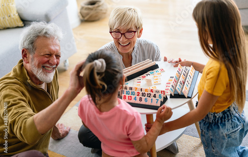 Happy grandparents having fun times with children at home