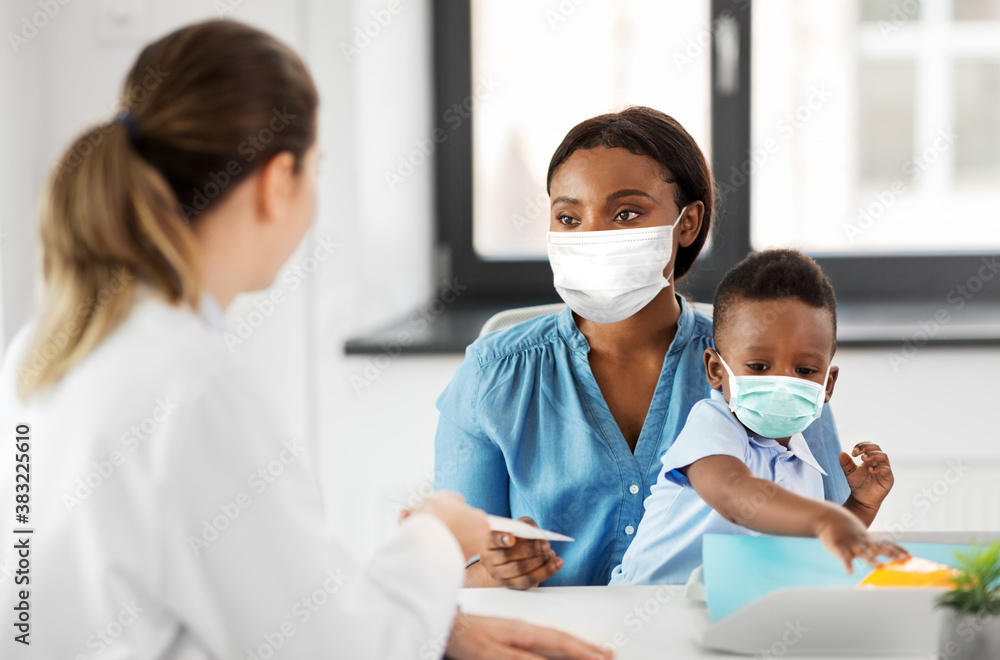 Fototapeta medicine, healthcare and pediatry concept - caucasian doctor giving prescription to african american mother wearing protective medical mask for protection from virus disease with baby son at clinic