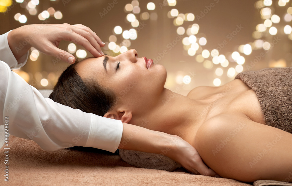 Fototapeta wellness, beauty and relaxation concept - beautiful young woman lying with closed eyes and having face and head massage at spa over festive lights on background