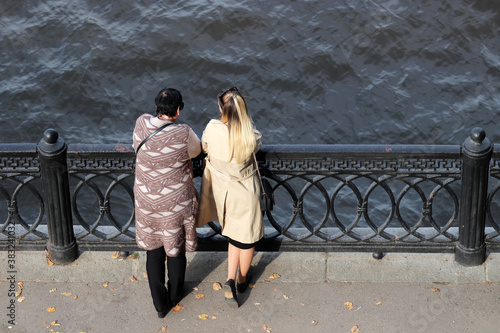 Two women in autumn clothes standing on a stone embankment on the river coast, t Wallpaper Mural
