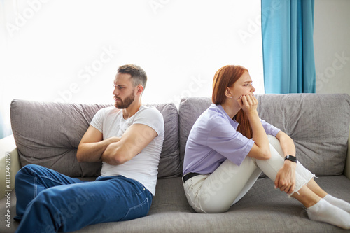 Fototapeta caucasian depressed redhead wife feeling upset after fight with husband, sit back to back. frustrated young girlfriend and boyfriend avoiding talk, couple tired of bad relationships, sit on sofa obraz