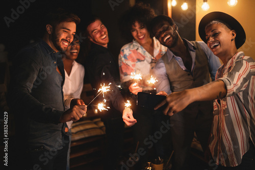 Happy friends celebrating with sparkler fireworks on new year's eve - Different Wallpaper Mural